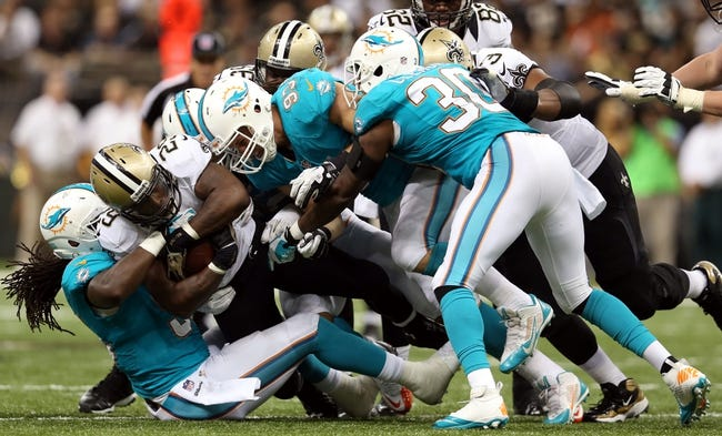 Sep 30, 2013; New Orleans, LA, USA; New Orleans Saints running back Khiry Robinson (29) is tackled by Miami Dolphins defenders during their game at the Mercedes-Benz Superdome. Mandatory Credit: Chuck Cook-USA TODAY Sports