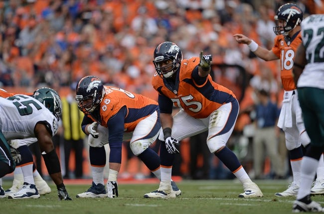 Sep 29, 2013; Denver, CO, USA; Denver Broncos guard Zane Beadles (68) and Denver Broncos tackle Chris Clark (75) at the line of scrimmage against the Philadelphia Eagles in the fourth quarter at Sports Authority Field at Mile High. Mandatory Credit: Ron Chenoy-USA TODAY Sports