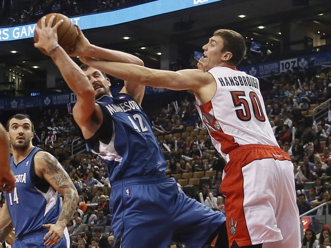 Oct 9, 2013; Toronto, Ontario, CAN; Toronto Raptors forward Tyler Hansbrough (50) tries to knock the ball away from Minnesota Timberwolves forward-center Kevin Love (42) during the first half at the Air Canada Centre. Mandatory Credit: John E. Sokolowski-USA TODAY Sports