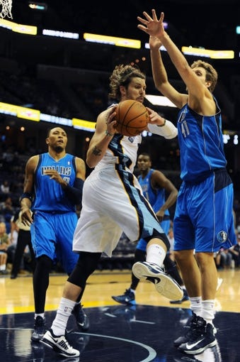 Oct 9, 2013; Memphis, TN, USA; Memphis Grizzlies small forward Mike Miller (center) grabs a rebound against Dallas Mavericks power forward Dirk Nowitzki (41)  at FedExForum. Mandatory Credit: Justin Ford-USA TODAY Sports