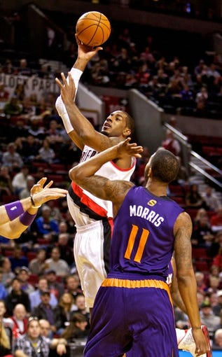 Oct 9, 2013; Portland, OR, USA; Portland Trail Blazers center LaMarcus Aldridge (12) shoots over Phoenix Suns power forward Markieff Morris (11) in the first quarter at the Moda Center. Mandatory Credit: Craig Mitchelldyer-USA TODAY Sports