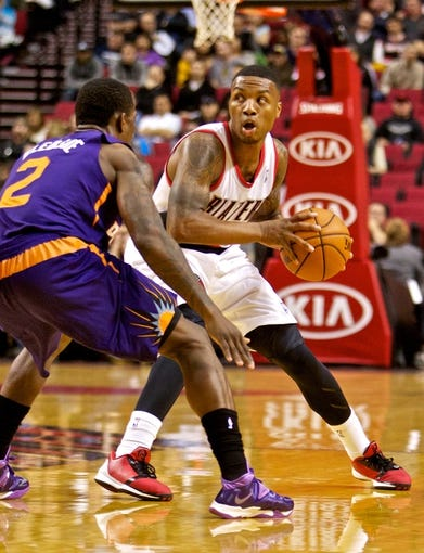 Oct 9, 2013; Portland, OR, USA; Portland Trail Blazers point guard Damian Lillard (0) looks to pass around Phoenix Suns point guard Eric Bledsoe (2) at the Moda Center. Mandatory Credit: Craig Mitchelldyer-USA TODAY Sports