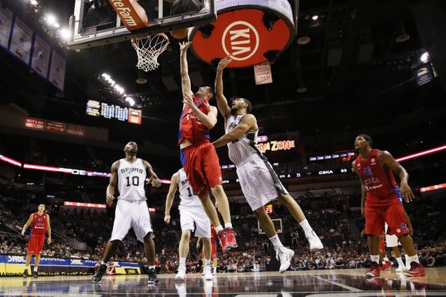 Oct 9, 2013; San Antonio, TX, USA; CSKA Moscow guard Vitaly Fridzon (left) drives to the basket past San Antonio Spurs forward Jeff Ayres (right) during the second half at the AT&T Center. The Spurs won 95-93 in overtime. Mandatory Credit: Soobum Im-USA TODAY Sports