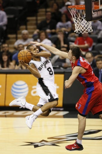 Oct 9, 2013; San Antonio, TX, USA; San Antonio Spurs guard Patrick Mills (8) is fouled while driving to the basket against CSKA Moscow guard Vitaly Fridzon (7) during the second half at the AT&T Center. The Spurs won 95-93 in overtime. Mandatory Credit: Soobum Im-USA TODAY Sports