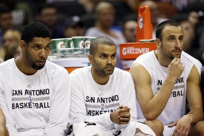Oct 9, 2013; San Antonio, TX, USA; San Antonio Spurs players (from left) Tim Duncan, and Tony Parker, and Manu Ginobili watch from the bench during the second half agains the CSKA Moscow at the AT&T Center. The Spurs won 95-93 in overtime. Mandatory Credit: Soobum Im-USA TODAY Sports