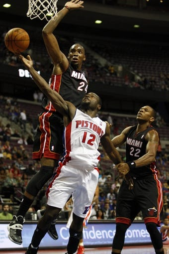 Oct 10, 2013; Auburn Hills, MI, USA; Detroit Pistons point guard Will Bynum (12) gets fouled by Miami Heat power forward Jarvis Varnado (24) during the fourth quarter at The Palace of Auburn Hills. Heat beat the Pistons 112-107. Mandatory Credit: Raj Mehta-USA TODAY Sports