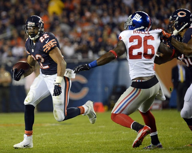 Oct 10, 2013; Chicago, IL, USA; Chicago Bears running back Matt Forte (22) rushes the ball against New York Giants strong safety Antrel Rolle (26) during the second half at Soldier Field. Chicago defeats New York 27-21. Mandatory Credit: Mike DiNovo-USA TODAY Sports
