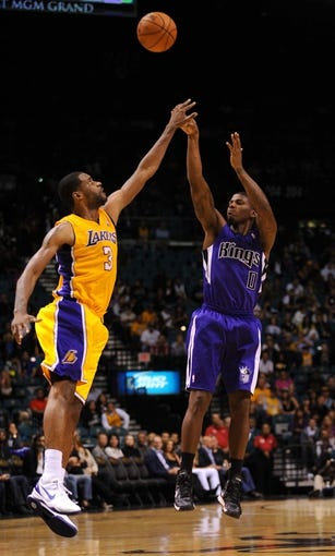 Oct 10, 2013; Las Vegas, NV, USA; Sacramento Kings forward DeQuan Jones (0) takes a three point shot against the defense of Los Angeles Lakers forward Shawne Williams (3) during an NBA preseason game at MGM Grand Arena. The Kings won the game 104-86. Mandatory Credit: Stephen R. Sylvanie-USA TODAY Sports