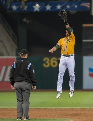 Oct 10, 2013; Oakland, CA, USA; Oakland Athletics shortstop Jed Lowrie (8) leaps to catch the throw from Oakland Athletics catcher Stephen Vogt (21, not pictured) during the sixth inning in game five of the American League divisional series playoff baseball game at O.co Coliseum. The Detroit Tigers defeated the Oakland Athletics 3-0. Mandatory Credit: Ed Szczepanski-USA TODAY Sports