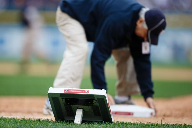 Oct 7, 2013; Detroit, MI, USA; Member of the grounds crew replaces first base during the seventh inning stretch in game three of the American League divisional series playoff baseball game between the Detroit Tigers and the Oakland Athletics at Comerica Park. Mandatory Credit: Rick Osentoski-USA TODAY Sports