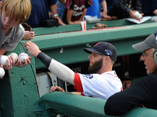 Oct 5, 2013; Boston, MA, USA; Boston Red Sox second baseman Dustin Pedroia (15) signs a baseball prior to the start of game two of the American League divisional series playoff baseball game against the Tampa Bay Rays at Fenway Park. Mandatory Credit: Bob DeChiara-USA TODAY Sports
