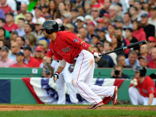 Oct 4, 2013; Boston, MA, USA; Boston Red Sox right fielder Shane Victorino (18) hits an RBI single during the fourth inning in game one of the American League divisional series playoff baseball game against the Tampa Bay Rays  at Fenway Park. Mandatory Credit: Bob DeChiara-USA TODAY Sports