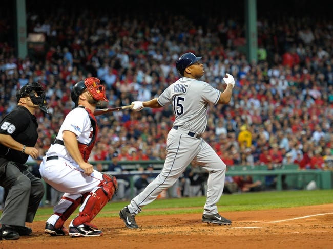 Oct 5, 2013; Boston, MA, USA; Tampa Bay Rays designated hitter Delmon Young (15) hits a sacrifice fly during the second inning in game two of the American League divisional series playoff baseball game against the Boston Red Sox at Fenway Park. Mandatory Credit: Bob DeChiara-USA TODAY Sports