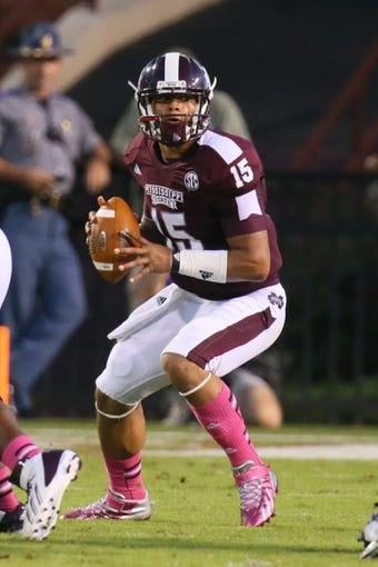 Oct 5, 2013; Starkville, MS, USA; Mississippi State Bulldogs quarterback Dak Prescott (15) drops back for a pass during the game against the LSU Tigers at Davis Wade Stadium.  LSU Tigers defeated the Mississippi State Bulldogs 59-26.  Mandatory Credit: Spruce Derden-USA TODAY Sports