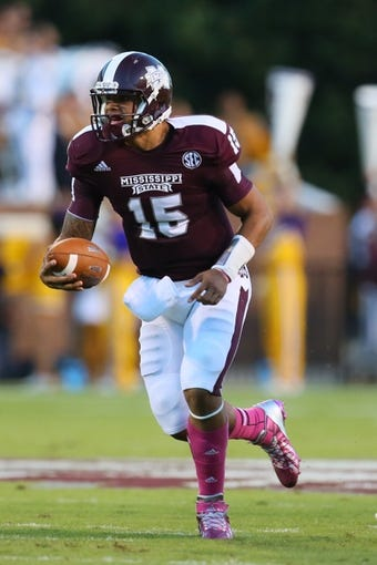 Oct 5, 2013; Starkville, MS, USA; Mississippi State Bulldogs quarterback Dak Prescott (15) advances the ball during the game against the LSU Tigers at Davis Wade Stadium.  LSU Tigers defeated the Mississippi State Bulldogs 59-26.  Mandatory Credit: Spruce Derden-USA TODAY Sports