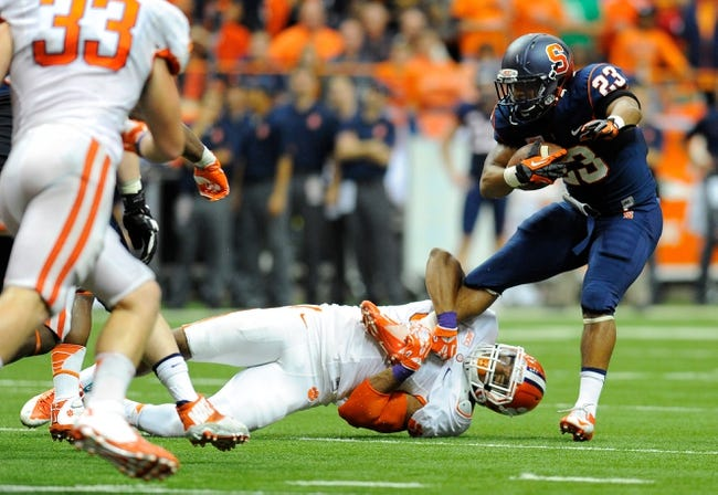 Oct 5, 2013; Syracuse, NY, USA; Syracuse Orange running back Prince-Tyson Gulley (23) is tackled by Clemson Tigers defensive end Vic Beasley (3) during the third quarter at the Carrier Dome.  Clemson defeated Syracuse 49-14.  Mandatory Credit: Rich Barnes-USA TODAY Sports