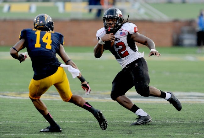 Oct 5, 2013; Kent, OH, USA; Northern Illinois Huskies running back Cameron Stingily (42) runs past the defense of Kent State Golden Flashes cornerback Dylan Farrington (14) during the fourth quarter at Dix Stadium. Northern Illinois beat Kent State 38-24. Mandatory Credit: Ken Blaze-USA TODAY Sports