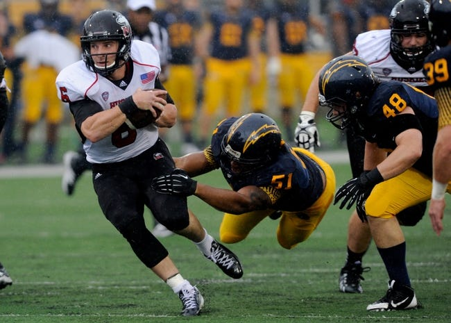 Oct 5, 2013; Kent, OH, USA; Northern Illinois Huskies quarterback Jordan Lynch (6) breaks the tackle of Kent State Golden Flashes defensive end Terrence Waugh (51) at Dix Stadium. Northern Illinois beat Kent State 38-24. Mandatory Credit: Ken Blaze-USA TODAY Sports