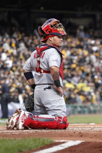 Oct 7, 2013; Pittsburgh, PA, USA; St. Louis Cardinals catcher Yadier Molina (4) waits for the pitcher to arrive on the mound against the Pittsburgh Pirates during the third inning in game four of the National League divisional series at PNC Park. The Cardinals won 2-1. Mandatory Credit: Charles LeClaire-USA TODAY Sports