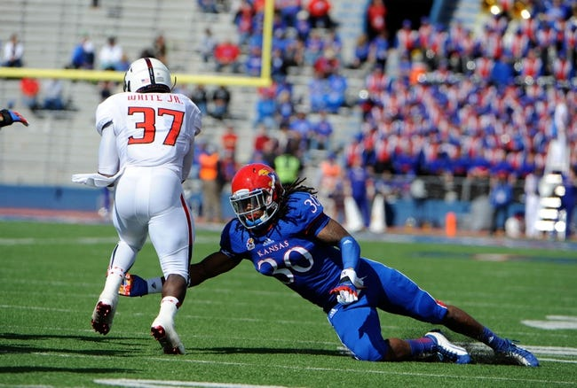 Oct 5, 2013; Lawrence, KS, USA; Kansas Jayhawks safety Tevin Shaw (30) tries to tackle Texas Tech Red Raiders running back Quinton White (37) in the second half at Memorial Stadium. Texas Tech won the game 54-16. Mandatory Credit: John Rieger-USA TODAY Sports