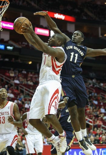 Oct 5, 2013; Houston, TX, USA; Houston Rockets small forward Ronnie Brewer (10) attempts to score during the fourth quarter as New Orleans Pelicans point guard Jrue Holiday (11) defends at Toyota Center. The Pelicans defeated the Rockets 116-115. Mandatory Credit: Troy Taormina-USA TODAY Sports