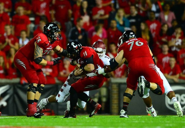 Oct 11, 2013; Cincinnati, OH, USA; Cincinnati Bearcats quarterback Brendon Kay (11) is sacked in the backfield during the third quarter against the Temple Owls at Nippert Stadium. Mandatory Credit: Andrew Weber-USA TODAY Sports