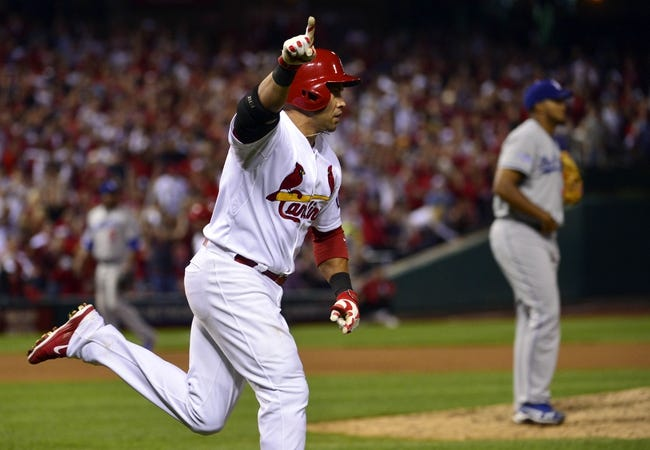 Oct 11, 2013; St. Louis, MO, USA; St. Louis Cardinals right fielder Carlos Beltran (left) celebrates after hitting the game-winning single off of Los Angeles Dodgers relief pitcher Kenley Jansen (background right) in the 13th inning in game one of the National League Championship Series baseball game at Busch Stadium. Mandatory Credit: Scott Rovak-USA TODAY Sports
