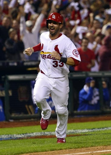 Oct 11, 2013; St. Louis, MO, USA; St. Louis Cardinals shortstop Daniel Descalso (33) scores the winning run in the 13th inning against the Los Angeles Dodgers  in game one of the National League Championship Series baseball game at Busch Stadium. Mandatory Credit: Scott Rovak-USA TODAY Sports