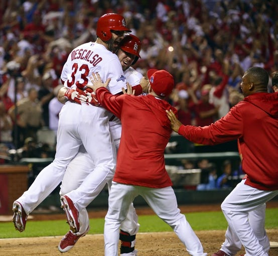Oct 11, 2013; St. Louis, MO, USA; St. Louis Cardinals shortstop Daniel Descalso (33) celebrates with teammates after scoring the winning run in the 13th inning against the St. Louis Cardinals in game one of the National League Championship Series baseball game at Busch Stadium. Mandatory Credit: Scott Rovak-USA TODAY Sports