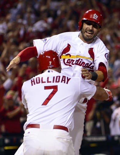 Oct 11, 2013; St. Louis, MO, USA; St. Louis Cardinals shortstop Daniel Descalso (rear) celebrates with left fielder Matt Holliday (7) after scoring the winning run in the 13th inning against the St. Louis Cardinals in game one of the National League Championship Series baseball game at Busch Stadium. Mandatory Credit: Scott Rovak-USA TODAY Sports