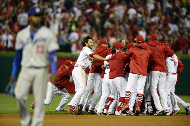 Oct 11, 2013; St. Louis, MO, USA; Members of the St. Louis Cardinals celebrate on the field as Los Angeles Dodgers shortstop Hanley Ramirez (foreground left) leaves the field following game one of the National League Championship Series baseball game at Busch Stadium. The Cardinals won 3-2 in 13 innings. Mandatory Credit: Jeff Curry-USA TODAY Sports