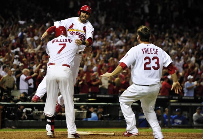 Oct 11, 2013; St. Louis, MO, USA; St. Louis Cardinals shortstop Daniel Descalso (rear) celebrates with teammates Matt Holliday (7) and David Freese (23) after scoring the winning run against the Los Angeles Dodgers in the 13th inning in game one of the National League Championship Series baseball game at Busch Stadium. Mandatory Credit: Scott Rovak-USA TODAY Sports