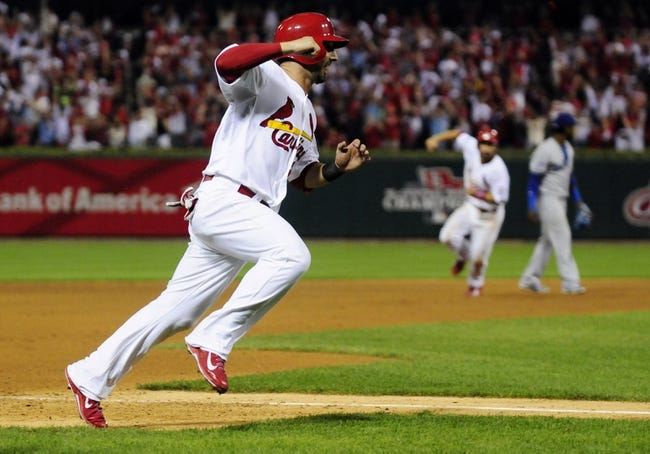 Oct 11, 2013; St. Louis, MO, USA; St. Louis Cardinals shortstop Daniel Descalso scores the winning run in the 13th inning against the Los Angeles Dodgers in game one of the National League Championship Series baseball game at Busch Stadium. Mandatory Credit: Jeff Curry-USA TODAY Sports