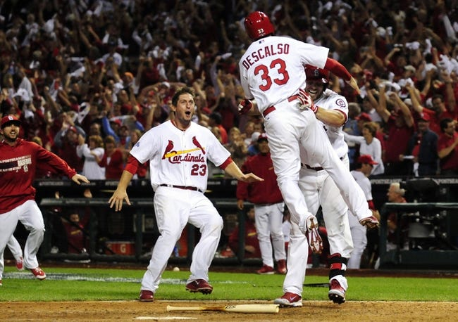 Oct 11, 2013; St. Louis, MO, USA; St. Louis Cardinals shortstop Daniel Descalso (33) celebrates with left fielder Matt Holliday (right) and third baseman David Freese (23) after scoring the winning run in the 13th inning against the Los Angeles Dodgers in game one of the National League Championship Series baseball game at Busch Stadium. Mandatory Credit: Jeff Curry-USA TODAY Sports