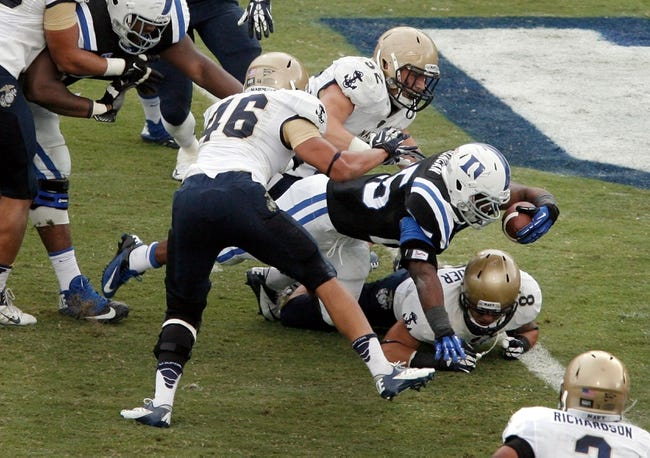 Oct 12, 2013; Durham, NC, USA; Duke Blue Devils running back Jela Duncan (25) reaches over Navy Midshipmen safety Wave Ryder (8) for a touchdown at Wallace Wade Stadium. Mandatory Credit: Mark Dolejs-USA TODAY Sports