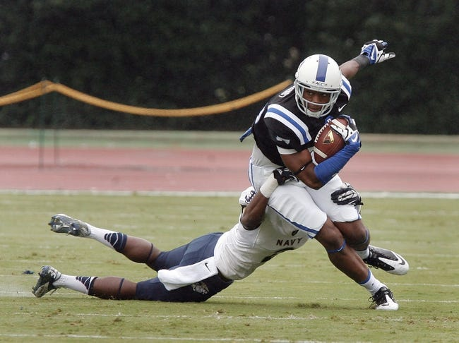 Oct 12, 2013; Durham, NC, USA; Navy Midshipmen cornerback Parrish Gaines (2) tackles Duke Blue Devils wide receiver Issac Blakeney (17) at Wallace Wade Stadium. Mandatory Credit: Mark Dolejs-USA TODAY Sports