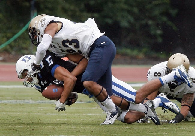 Oct 12, 2013; Durham, NC, USA; Navy Midshipmen safety Chris Ferguson (23) tackles Duke Blue Devils wide receiver Brandon Braxton (5) in their game at Wallace Wade Stadium. Mandatory Credit: Mark Dolejs-USA TODAY Sports