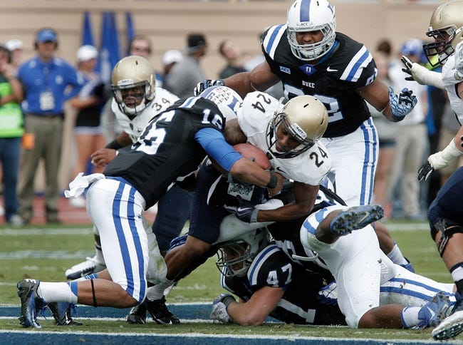 Oct 12, 2013; Durham, NC, USA; Duke Blue Devils safety Jeremy Cash (16) tackles Navy Midshipmen running back Ryan Williams-Jenkins (24) in their game at Wallace Wade Stadium. Mandatory Credit: Mark Dolejs-USA TODAY Sports