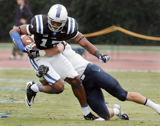 Oct 12, 2013; Durham, NC, USA; Navy Midshipmen linebacker Cody Peterson (53) tackles Duke Blue Devils wide receiver Issac Blakeney (17) in their game at Wallace Wade Stadium. Mandatory Credit: Mark Dolejs-USA TODAY Sports