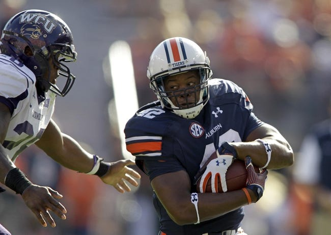 Oct 12, 2013; Auburn, AL, USA; Auburn Tigers running back Chandler Shakespeare (42) avoids Western Carolina Catamounts defensive back Ace Clark (28) during the second half at Jordan Hare Stadium.  The Tigers beat the Catamounts 62-3. Mandatory Credit: John Reed-USA TODAY Sports