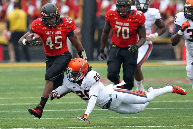 Oct 12, 2013; College Park, MD, USA; Maryland Terrapins running back Brandon Ross (45) runs past a diving Virginia Cavaliers cornerback Maurice Canady (26) at Byrd Stadium. Mandatory Credit: Mitch Stringer-USA TODAY Sports