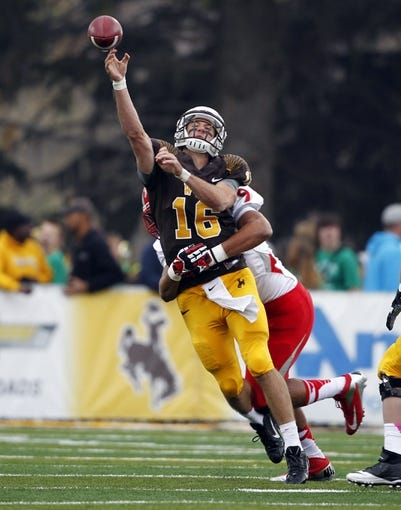 Oct 12, 2013; Laramie, WY, USA; Laramie, WY, USA; Wyoming Cowboys quarterback Brett Smith (16) is tackled by New Mexico Lobos linebacker Richard Winston (9) during the first quarter at War Memorial Stadium. Mandatory Credit: Troy Babbitt-USA TODAY Sports