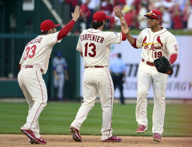 Oct 12, 2013; St. Louis, MO, USA; St. Louis Cardinals players Daniel Descalso (33) , Matt Carpenter (13) and Jon Jay (19) celebrate after game two of the National League Championship Series baseball game against the Los Angeles Dodgers at Busch Stadium. Mandatory Credit: Scott Rovak-USA TODAY Sports