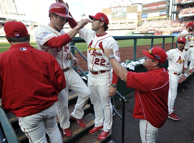Oct 12, 2013; St. Louis, MO, USA; St. Louis Cardinals third baseman David Freese (23) is welcomed back to the dugout by manager Mike Matheny (22) after scoring a run against the Los Angeles Dodgers in the fifth inning in game two of the National League Championship Series baseball game at Busch Stadium. Mandatory Credit: Scott Rovak-USA TODAY Sports