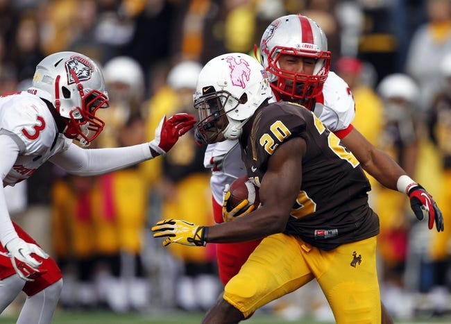 Oct 12, 2013; Laramie, WY, USA; Laramie, WY, USA; Wyoming Cowboys return specialist Blair Burns (20) runs the ball against New Mexico Lobos cornerbacks Cranston Jones (3) and Dante Caro (31) during the third quarter at War Memorial Stadium. The Cowboys beat the Lobos 38-31. Mandatory Credit: Troy Babbitt-USA TODAY Sports
