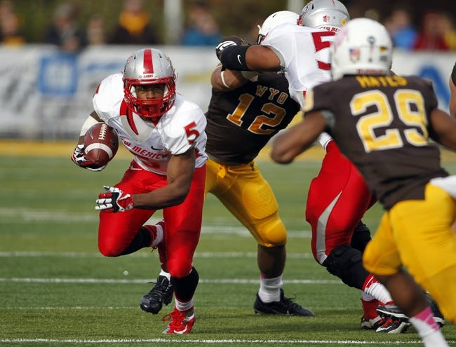 Oct 12, 2013; Laramie, WY, USA; Laramie, WY, USA; New Mexico Lobos running back Kasey Carrier (5) runs against Wyoming Cowboys cornerback Tim Hayes (29) during the third quarter at War Memorial Stadium. The Cowboys beat the Lobos 38-31. Mandatory Credit: Troy Babbitt-USA TODAY Sports