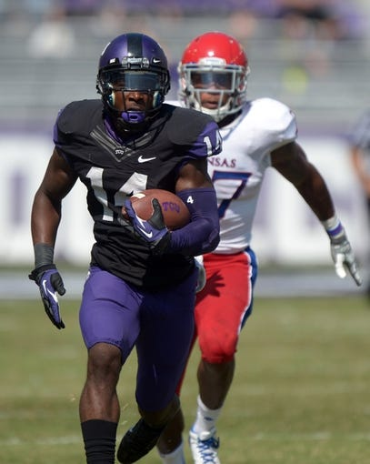Oct 12, 2013; Fort Worth, TX, USA; TCU Horned Frogs receiver David Porter (14) is pursued by Kansas Jayhawks cornerback Victor Simmons (27) on a 75-yard touchdown reception in the third quarter at Amon G. Carter Stadium. TCU defeated Kansas 27-17. Mandatory Credit: Kirby Lee-USA TODAY Sports
