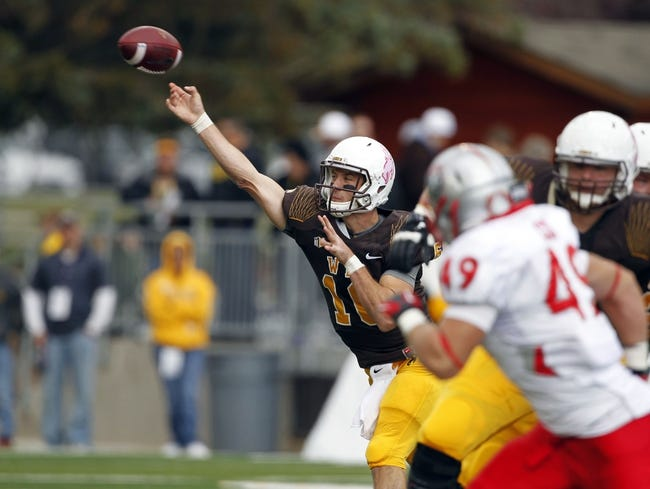 Oct 12, 2013; Laramie, WY, USA; Laramie, WY, USA; Wyoming Cowboys quarterback Brett Smith (16) throws against New Mexico Lobos linebacker Dakota Cox (49) during the second quarter at War Memorial Stadium. The Cowboys beat the Lobos 38-31. Mandatory Credit: Troy Babbitt-USA TODAY Sports