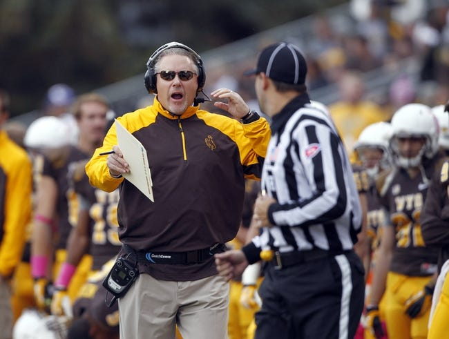 Oct 12, 2013; Laramie, WY, USA; Laramie, WY, USA; Wyoming Cowboys head coach Dave Christensen talks to an official against the New Mexico Lobos  during the third quarter at War Memorial Stadium. The Cowboys beat the Lobos 38-31. Mandatory Credit: Troy Babbitt-USA TODAY Sports