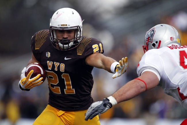 Oct 12, 2013; Laramie, WY, USA; Laramie, WY, USA; Wyoming Cowboys running back Shaun Wick (21) stiff arms New Mexico Lobos linebacker Dallas Bollema (41) during the first quarter at War Memorial Stadium. The Cowboys beat the Lobos 38-31. Mandatory Credit: Troy Babbitt-USA TODAY Sports